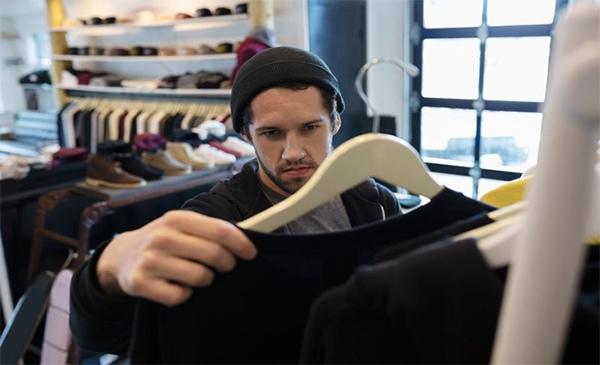 chàng trai xem áo tại cửa hàng